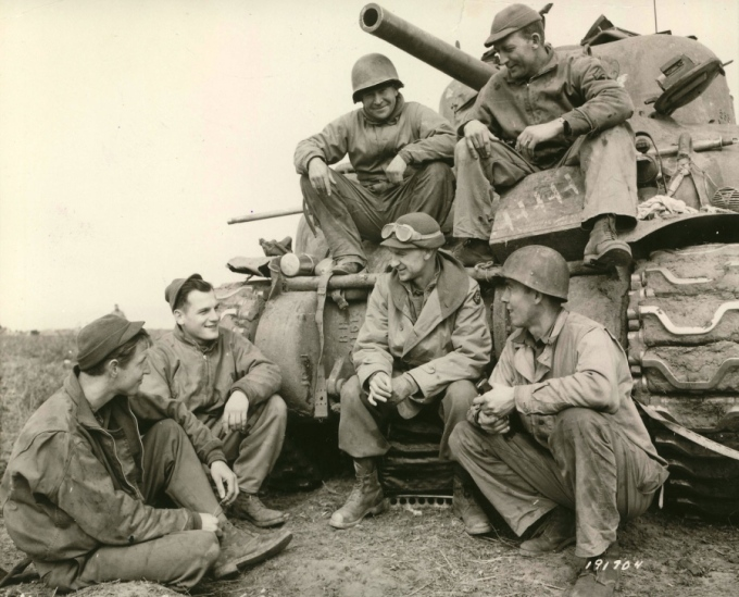 With goggles atop his head, Ernie Pyle talks to a group of soldiers near Anzio, Italy